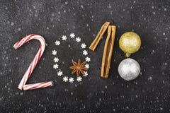 Nieuwjaarachtergrond van sneeuwvlokken, snoepjes, suikergoed, kaneel, het jaar 2018 van het ballenaantal Stock Afbeeldingen