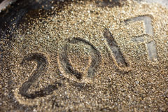 2017 nieuwjaarconcept Nummer 2017 op de gouden zandtextuur Stock Fotografie