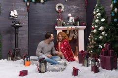 Nieuwjaardecoratie en romantische paarzitting dichtbij de brandplaats royalty-vrije stock foto's