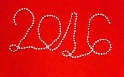 2016 nieuwjaarinschrijving van witte geparelde halsband wordt gemaakt die Stock Afbeeldingen