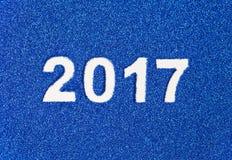Nieuwjaarnummer 2017 geschreven op achtergrond van blauwe schitterende lovertjes Royalty-vrije Stock Fotografie