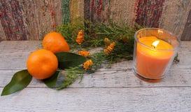 Nieuwjaarsamenstelling met mandarijnen, arborvitaetak, kaarsen en Kerstbomen Royalty-vrije Stock Afbeelding