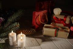 Nieuwjaarsamenstelling van de kegels en de verpakte giften in dark Het licht van de gloeiende kaarsen Stock Afbeelding