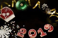 Nieuwjaarskaart op zwarte achtergrondpeperkoek rode nummer 2019 met multi-colored sterren, gouden wimpel, rode vuisthandschoen stock fotografie