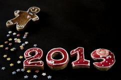 Nieuwjaarskaart op zwarte achtergrondpeperkoek rode nummer 2019 met multi-colored sterren, peperkoekmens royalty-vrije stock fotografie