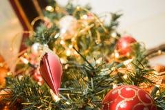 Nieuwjaarsnuisterijen op verfraaide Kerstboom met vage achtergrond Stock Foto's