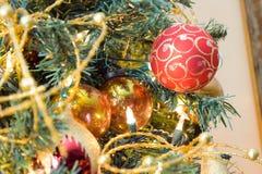 Nieuwjaarsnuisterijen op verfraaide Kerstboom met vage achtergrond Stock Afbeeldingen