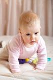 Nieuwsgierig babymeisje dat op bed, close-upschot kruipt Royalty-vrije Stock Foto's