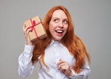 Nieuwsgierig meisje dat een huidige doos schudt Stock Afbeeldingen