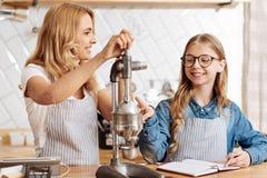 Nieuwsgierig meisje die op het koffie-makend apparaat richten stock afbeeldingen
