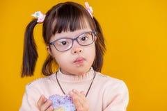 Nieuwsgierig mooi kind met chromosoomabnormaliteit die kruimeltaarten hebben royalty-vrije stock foto