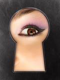 Nieuwsgierig vrouwelijk oog in een sleutelgat Stock Afbeeldingen
