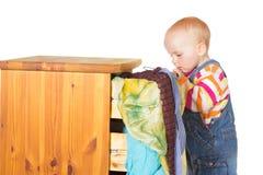 Nieuwsgierig weinig baby die in een lade tuurt Stock Foto's