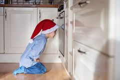 Nieuwsgierig weinig jongen, het letten op de koekjes van het gemberbrood in de oven stock fotografie