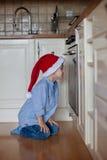 Nieuwsgierig weinig jongen, het letten op de koekjes van het gemberbrood in de oven Royalty-vrije Stock Foto's
