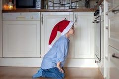 Nieuwsgierig weinig jongen, het letten op de koekjes van het gemberbrood in de oven Stock Foto's