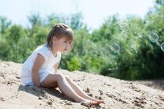 Nieuwsgierig weinig modelzitting op zand in park Stock Fotografie
