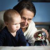 Nieuwsgierige baby en zijn grootmoeder stock afbeeldingen