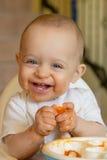 Nieuwsgierige babyjongen die een abrikoos eet Stock Fotografie