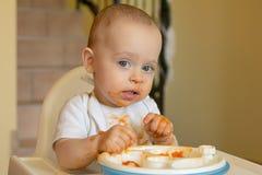 Nieuwsgierige babyjongen die een abrikoos eet Stock Afbeeldingen