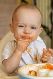 Nieuwsgierige babyjongen die een abrikoos eet Stock Foto's