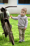 Nieuwsgierige Babyjongen die rond de oude fiets lopen Stock Afbeeldingen