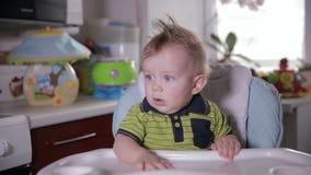 Nieuwsgierige grappige baby die, als babyvoorzitter zitten rond kijken die stock footage