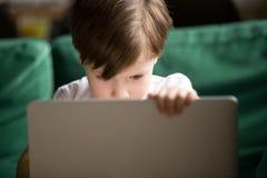 Nieuwsgierige jong geitjejongen die in het geheim op verboden gecensureerde inhoud letten royalty-vrije stock afbeeldingen
