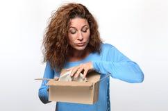 Nieuwsgierige jonge vrouw die binnen een giftdoos gluurt stock afbeelding