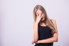 Nieuwsgierige jonge vrouw die gezicht behandelen met hand en camera bekijken terwijl status tegen grijze achtergrond Stock Foto's