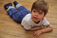 Nieuwsgierige kleine jongen die op houten vloer ligt stock afbeelding