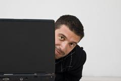 Nieuwsgierige mens die behing laptop kijkt Royalty-vrije Stock Afbeeldingen