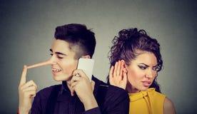 Nieuwsgierige ongerust gemaakte vrouw die in het geheim aan een gelukkige man leugenaar luisteren die op mobiele telefoon met zij royalty-vrije stock afbeelding