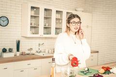 Nieuwsgierige praatzieke vrouw die gesprek hebben door smartphone royalty-vrije stock afbeelding