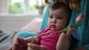 Nieuwsgierige ruikende de tulpenbloem van het babymeisje stock video