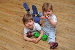 Nieuwsgierige siblings die en op houten vloer zitten liggen royalty-vrije stock afbeelding