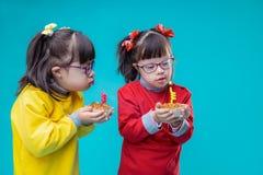 Nieuwsgierige tweelingzusters met geestelijke wanorde die vakantiecakes onderzoeken stock foto's