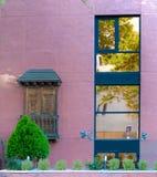 Nieuwsgierige voorgevel in roze waar de nieuwe stijlen van vensters met klassiek gezichtspunt of weinig terras worden gemengd stock fotografie
