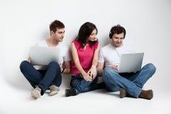 Nieuwsgierige vrienden die laptop bekijken Stock Foto's