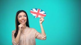 Nieuwsgierige vrouw die Brits vlagteken in het buitenland houden, lerend taal, onderwijs stock footage