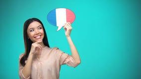 Nieuwsgierige vrouw die Frans vlagteken in het buitenland houdt, lerend taal, onderwijs stock footage