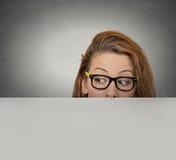 Nieuwsgierige vrouw die over rand van leeg leeg document aanplakbord gluren Royalty-vrije Stock Fotografie