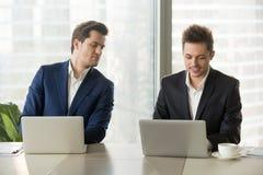 Nieuwsgierige zakenman die in het geheim collegalaptop het scherm bekijken, royalty-vrije stock foto's