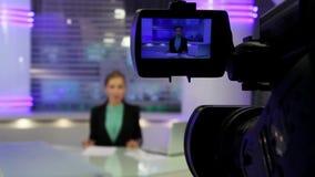 Nieuwsstudio Het jonge en mooie nieuws van de meisjeslezing op televisie stock videobeelden
