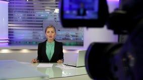 Nieuwsstudio Het jonge en mooie nieuws van de meisjeslezing op televisie stock video