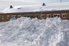 Nieve acumulada por la ventisca delante de una casa del ladrillo Imágenes de archivo libres de regalías