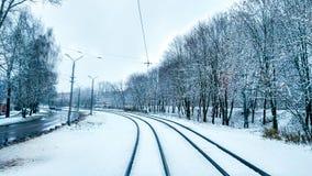 Nieve blanca en ciudad en un tranvía en noviembre, primera nieve diciembre Ciudad nevada con los árboles en invierno Cerca durmie imagen de archivo