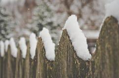 Nieve caida en una cerca rústica Fotos de archivo libres de regalías