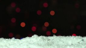 Nieve con el centelleo de luces blured del bokeh de la guirnalda en fondo oscuro metrajes