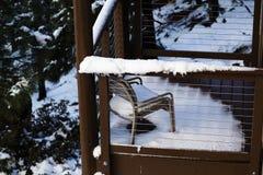 Nieve de fusión en el pequeño pórtico de madera con la silla Imagen de archivo